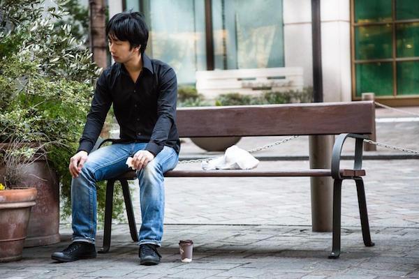 ひとりぼっちでベンチに座る男性の画像